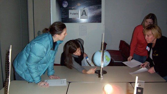 An Adler Planetarium educator and teacher workshop participants participate in a Reasons for the Seasons demonstration using an Earth globe and a bright light to represent the Sun.